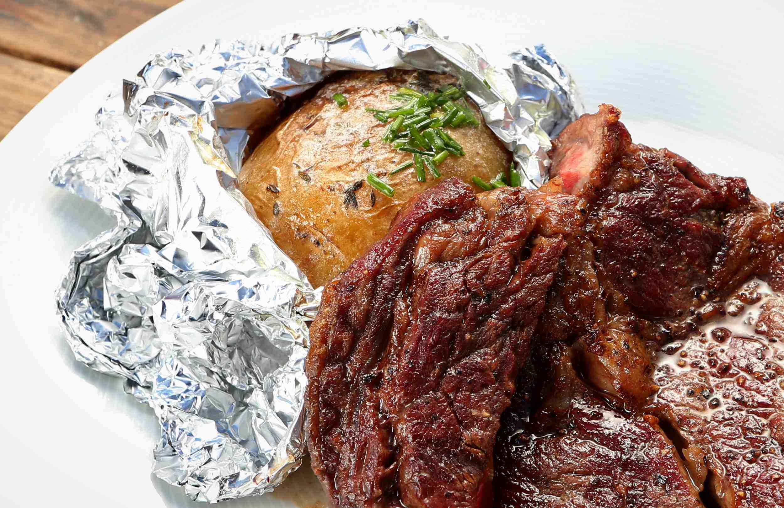 Rib eye steak spečenými bramborami na grilu