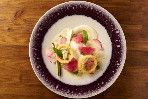 Halibut pošírovaný v uzeném másle, ředkvičky, růžová ředkev, jarní cibulky, pyré z bílé cibule, smažené cibulové kroužky a beurre blanc s estragonem  Foto: