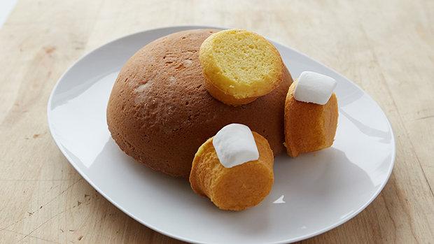 Muffinům lehce seřízněte vršky. Půlkulatý korpus položte na talíř vypouklou stranou nahoru a přilepte na něj pomocí krému muffiny. Na dva muffiny po stranách pak ještě přilepte murshmallow.  Foto: