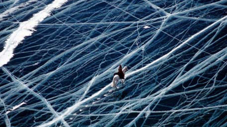 Jízda na koni po zamrzlém jezeře v horách Pamír.
