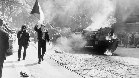 Pražané s vlajkou, v pozadí hořící invazní tank