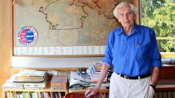 Mapa světa se zaznamenanou trasou a u ní stojící Miroslav Zikmund