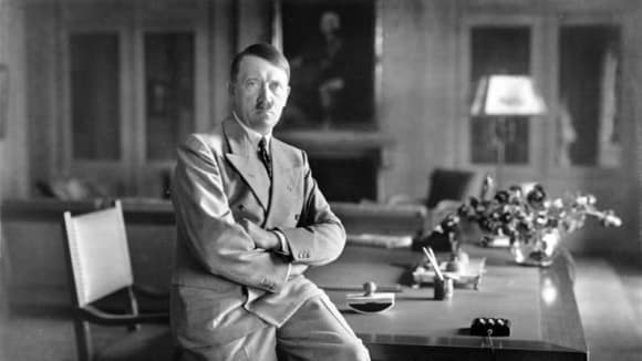 Adolf Hitler ve své pracovně - pevně založené ruce možná měly před fotografem zakrýt třes