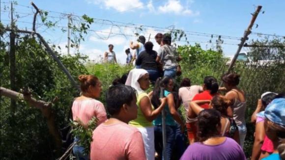 Příbuzní vězňů se snaží dostat skrze plot do areálu