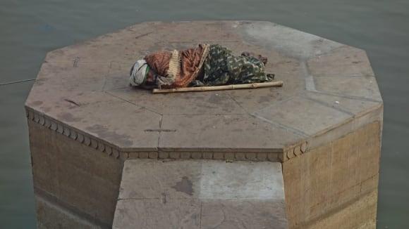 Poutník u řeky Ganga, Váránasí, Indie