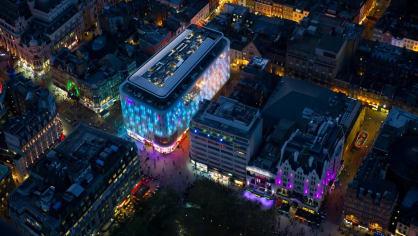 W London Leicester Square s prosvětlenou fasádou, která mění během dne barvu