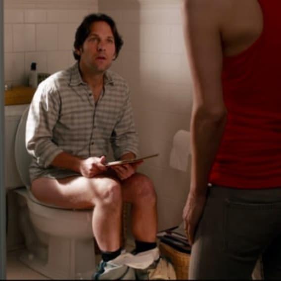 Muž sedí na záchodě